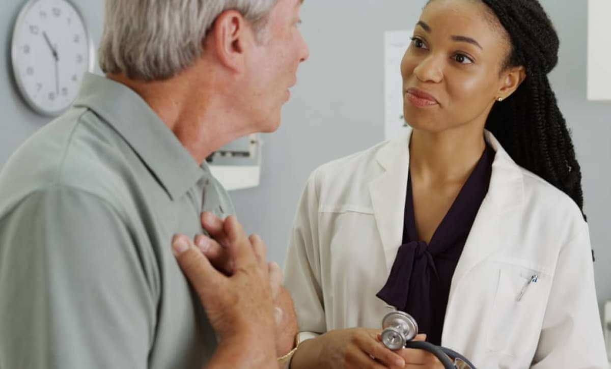African American nurse practitioner talking to elderly male patient